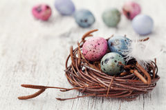 Painted easter eggs in nest on rustic wooden background, vintage style Royalty Free Stock Photo