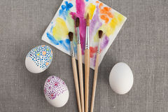Decoration Easter eggs. Painted Easter eggs and paintbrushes Stock Photo