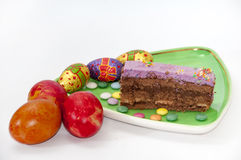 Painted easter eggs and a piece of chocolate cake Royalty Free Stock Photography