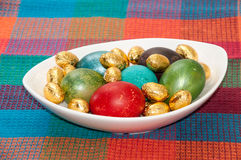 Painted Easter eggs in a white bowl on the kitchen tablecloth Stock Photos