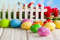 Easter eggs and white fence on wooden and grass background. Painted Easter eggs and white fence on wooden and grass background royalty free stock images