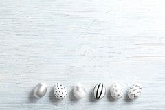 Painted Easter eggs on wooden background, flat lay. With space for text royalty free stock photos