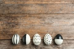 Painted Easter eggs on wooden background, flat lay. With space for text stock photography