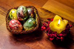 Painted Easter Eggs. In wooden basket with candle on the side Royalty Free Stock Photo