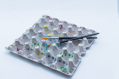 Painted egg box carton with brushes Royalty Free Stock Photography