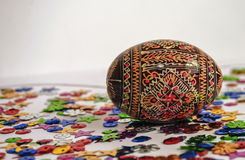 A painted egg in colorful confetti. Royalty Free Stock Images
