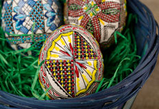 Painted eggs in basket. Beautiful painted eggs in a basket on wood background Royalty Free Stock Image