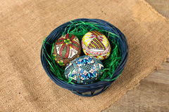 Painted eggs. Beautiful painted eggs in a basket on wood background Royalty Free Stock Photography