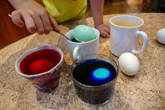 Boy paints eggs for Easter, use spoon dips eggs into colored water in the home interior. Painted eggs for Easter, process, different colors - yellow, green. 3-4 royalty free stock photography