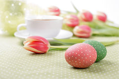 Painted eggs and tulips around a tea cup Royalty Free Stock Photo
