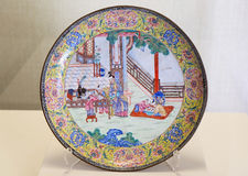 Painted enamel round plate from Qing Dynasty in Forbidden City, Beijing. Painted enamel round plate with designs of beautiful ladies and five children from Qing royalty free stock photography