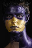 Painted face. Portrait of young handsome male model wearing artistic bodypaint drawing Royalty Free Stock Images