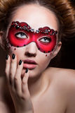 Painted Face. Beautiful Girl in Red Carnival Mask. Masquerade Stock Photo