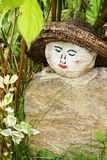 Painted face on rock garden decoration. Original homemade garden decoration with round painted rock as a woman's face with straw hat hidden amongst the hedge Royalty Free Stock Photos