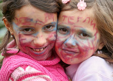 Painted faces. Young girls with faces painted with make-up colors Royalty Free Stock Image