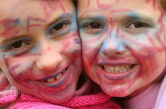 Painted faces. Two beautifull young girls with faces painted with make-up colors Stock Photos