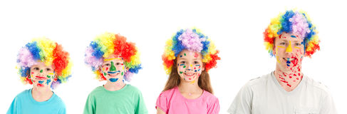 Painted faces clown wigs on family of dad and kids. Kids and Dad with painted faces and clown wigs. Isolated on white Stock Photo