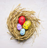 Painted with the faces of family members decorative eggs for Easter, in the nest wooden rustic background top view close up Royalty Free Stock Photos