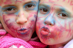 Painted faces kissing Stock Images