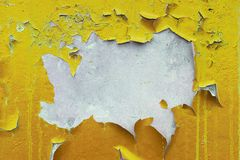 Painted, faded, plastered, walls with peeling yellow and orange paint. Worn out old concrete details close up. Textured background stock image
