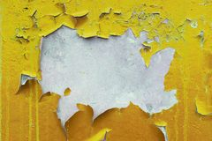 Painted, faded, plastered, walls with peeling yellow and orange paint. Worn out old concrete details close up. Textured background stock images
