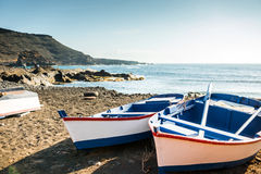 Painted fishing boats on Canary Island shore in bay Stock Photos
