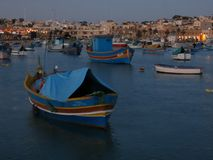 Painted fishing boats, Marsaxlokk, Malta. Colorful painted wooden fishing boats in harbor of Marsaxlokk, Malta at daybreak Royalty Free Stock Photography