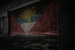 Painted flag of antigua and barbuda on the dirty old wall in an abandoned ruined house. Concept stock photography