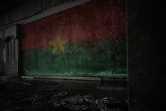 Painted flag of burkina faso on the dirty old wall in an abandoned ruined house. Concept stock images