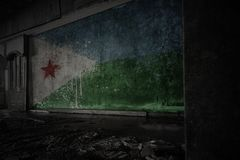 Painted flag of djibouti on the dirty old wall in an abandoned ruined house. Concept stock photography