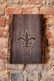 Painted Fleur de Lis on natural wooden slab against an old exposed brick wall. Home decor. Interior design. Exposed brick wall. Exposed brick wall with Fleur de Royalty Free Stock Photos