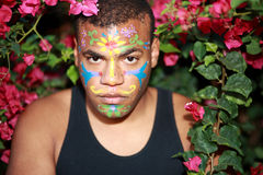 Painted flowers on black man. Portrait of young black man with painted face, framed by blooming red flowers Royalty Free Stock Photography