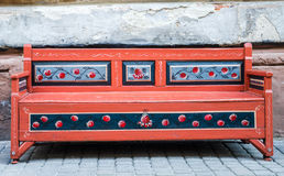 A painted flowers old vintaga red wooden bench on a city street. A painted flowers old vintaga red wooden bench Royalty Free Stock Images