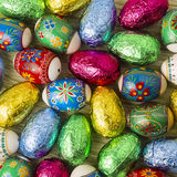 Painted and foil Easter Eggs. Painted Easter Eggs and foil covered chocolate Easter eggs for traditional Easter celebration Stock Photo