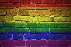 Painted gay pride rainbow flag on a brick wall. Colorful painted gay pride rainbow flag on a old brick wall royalty free stock photography