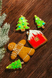 Painted gingerbread house, Christmas tree and the man on a wooden background Stock Photography