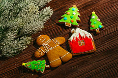 Painted gingerbread house, Christmas tree and the man on a wooden background Stock Photos