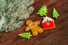 Painted gingerbread house, Christmas tree and the man on a wooden background Royalty Free Stock Photography