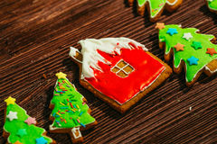 Painted gingerbread house, Christmas tree on a wooden background Royalty Free Stock Image