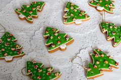 Painted gingerbread in the shape of Christmas tree on a white napkin background. Christmas trees cookies - colorful. Icing decoration Stock Photo