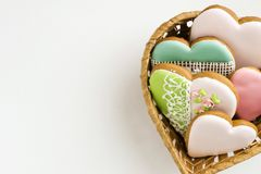 Painted gingerbread in a straw basket. Bakery products. Gingerbread in the shape of a heart. Place for text. Gingerbread pattern royalty free stock images