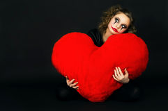 Painted girl holding a big heart Stock Photo