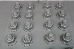 Painted gray bolts with thread with screwed nuts on the metal panel Royalty Free Stock Image