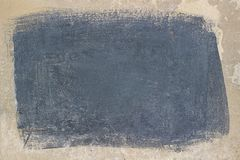 Painted gray rectangle on a beige concrete surface. Plastered wall with a gray rectangle in the center. Gray background with beige frame as design elements or a Stock Image