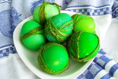 painted green eggs decorated with a rope for Easter Stock Photos