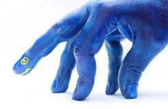 Painted hand, blue dinosaur. Hand painted in blue paint with yellow eye and mouth, resembles dinosaur royalty free stock photos