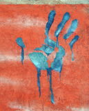 Painted hand print. Blue hand print painted on red wall - street art Stock Image