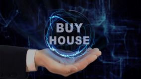 Painted hand shows concept hologram Buy house on his hand. Drawn man in business suit with future technology screen and modern cosmic background Stock Photos