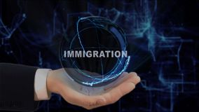 Painted hand shows concept hologram Immigration on his hand. Drawn man in business suit with future technology screen and modern cosmic background Royalty Free Stock Photo