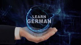 Painted hand shows concept hologram Learn German on his hand. Drawn man in business suit with future technology screen and modern cosmic background stock video footage